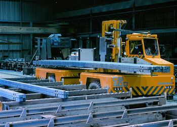 Large Baumann sideloader in a metal mill carrying long pieces of steal.