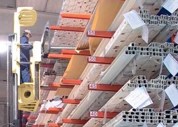 Man on man-up order picker picking extrusions off a cantilever rack system