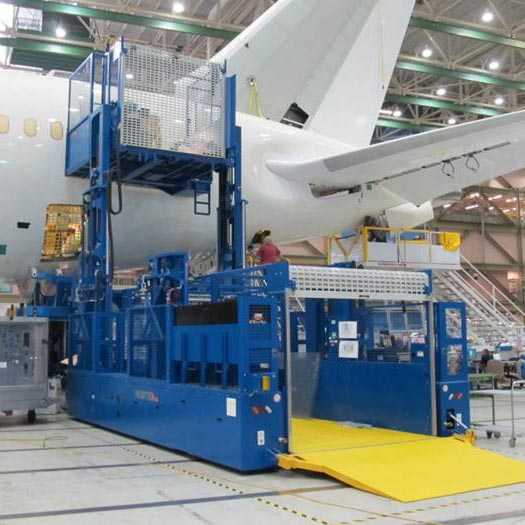 Material lifter attached to an airplane in assembly