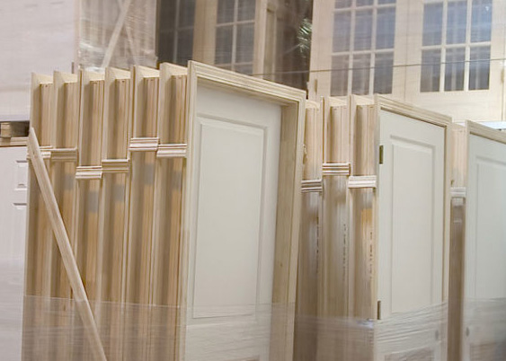 Close-up of wooden doors and frames stored in a warehouse on pallets