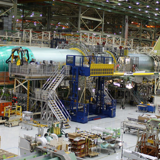 Material lifter docked to an airplane in a manufacturing line