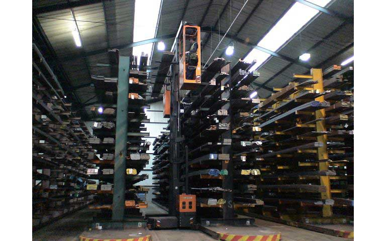 Hubtex model MU-SO two-man order picking metal profiles off cantilever racking in a narrow aisle