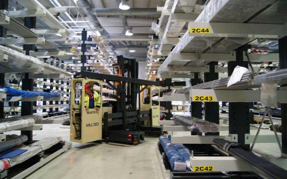 Hubtex model MU-SO two-man order moving through cantilever racking in a narrow aisle