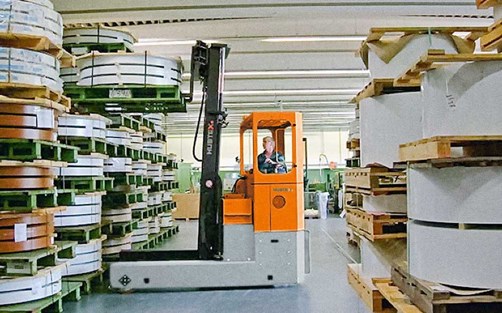 HUBTEX Reach Truck loading coiled plastic on to rack