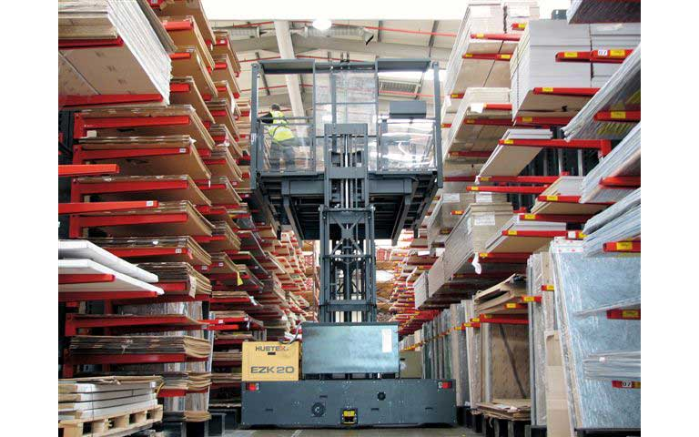 Hubtex EZK Order Picker with order picking platform picking sheet rock from both sides in a narrow aisle