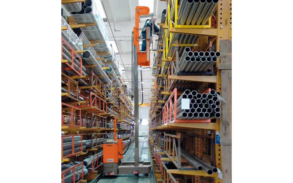 Hubtex Man Up Order Picker man at highest cantilever rack picking metal tubes