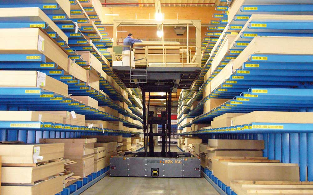 Hubtex EZK Order Picker with order picking platform picking boxed windows from both sides in a narrow aisle