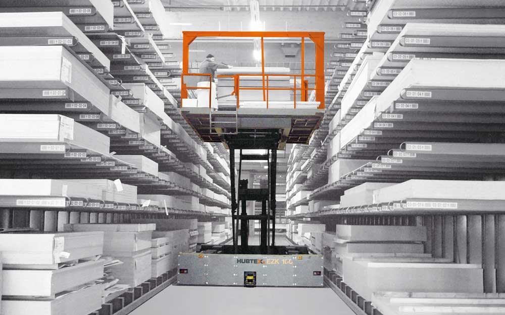 Hubtex EZK Order Picker with order picking platform picking engineered wood sheet from both sides in a narrow aisle