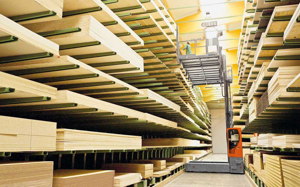 Hubtex KP Order Picking System with removable order picking platform at top shelf of cantilever rack picking ply wood