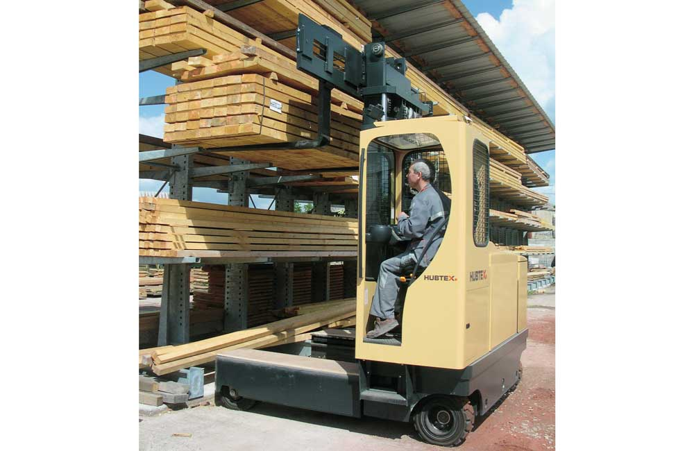 Hubtex 2125 Electric Multidirectional Sideloader placing lumber on a cantilever rack outdoors