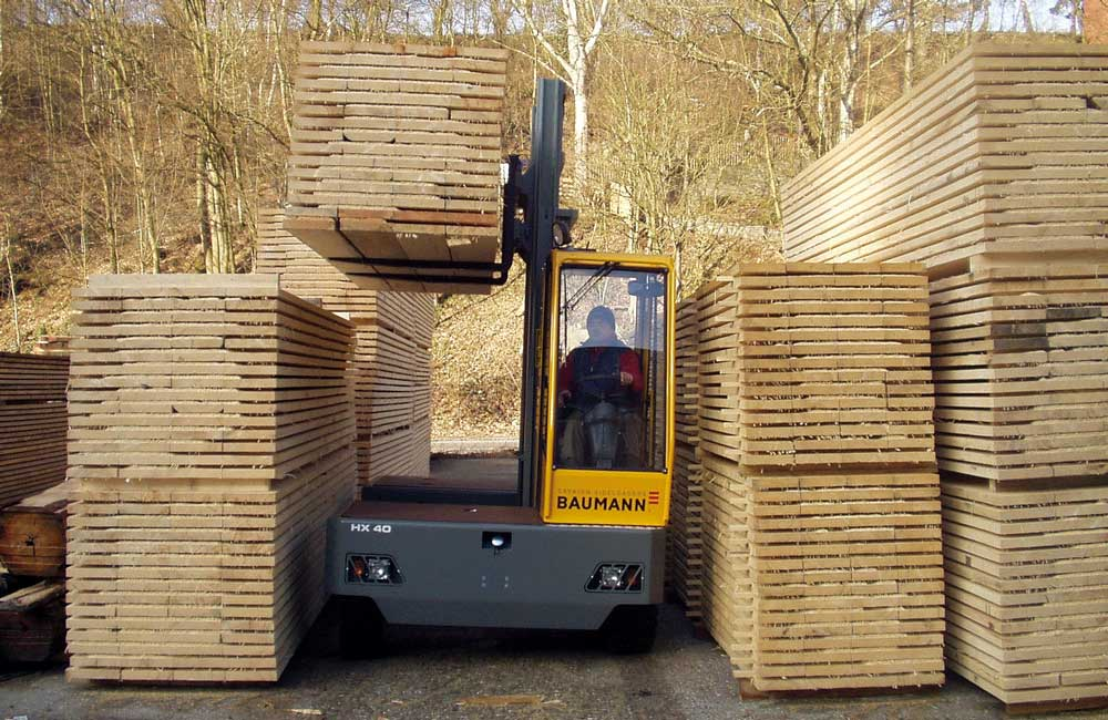 Baumann HX 40 lifting large load of lumber in narrow aisle outdoor
