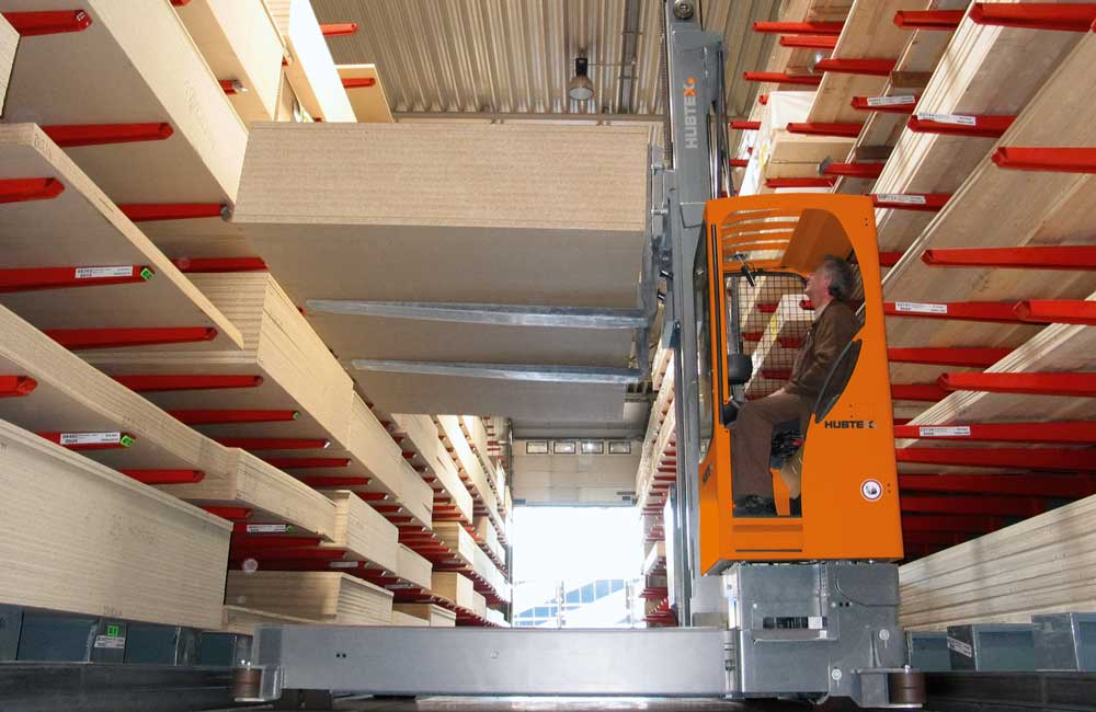 Hubtex electric multidirectional sideloader lifting engineered wood off a cantilever rack system