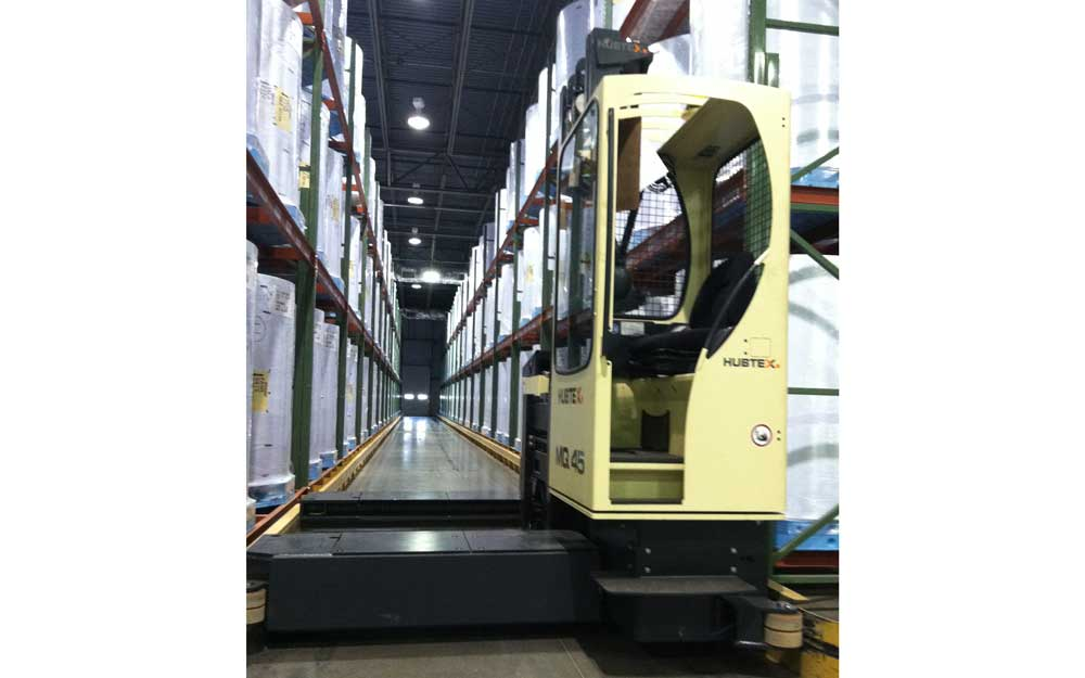Hubtex MQ 45 Electric Multidirectional Sideloader in narrow aisle of pallet rack holding upright rolls of plastic