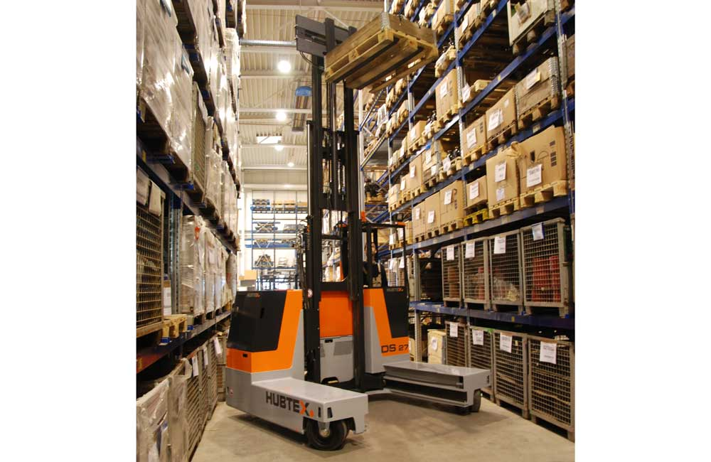 Hubtex 3-Wheel Electric Multidirectional Sideloader moving product from pallet racking