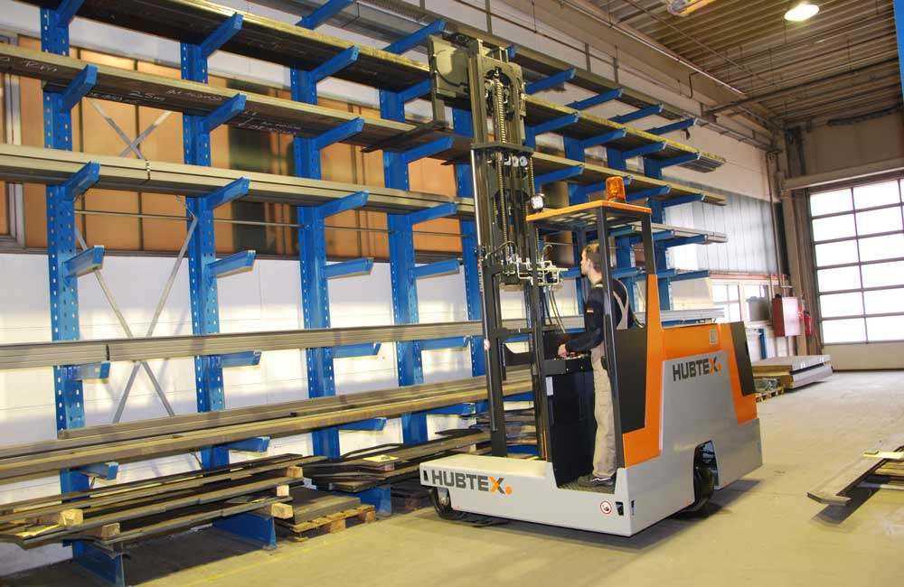 Hubtex 3-Wheel Electric Multidirectional Sideloader moving wood bundles from cantilever racking