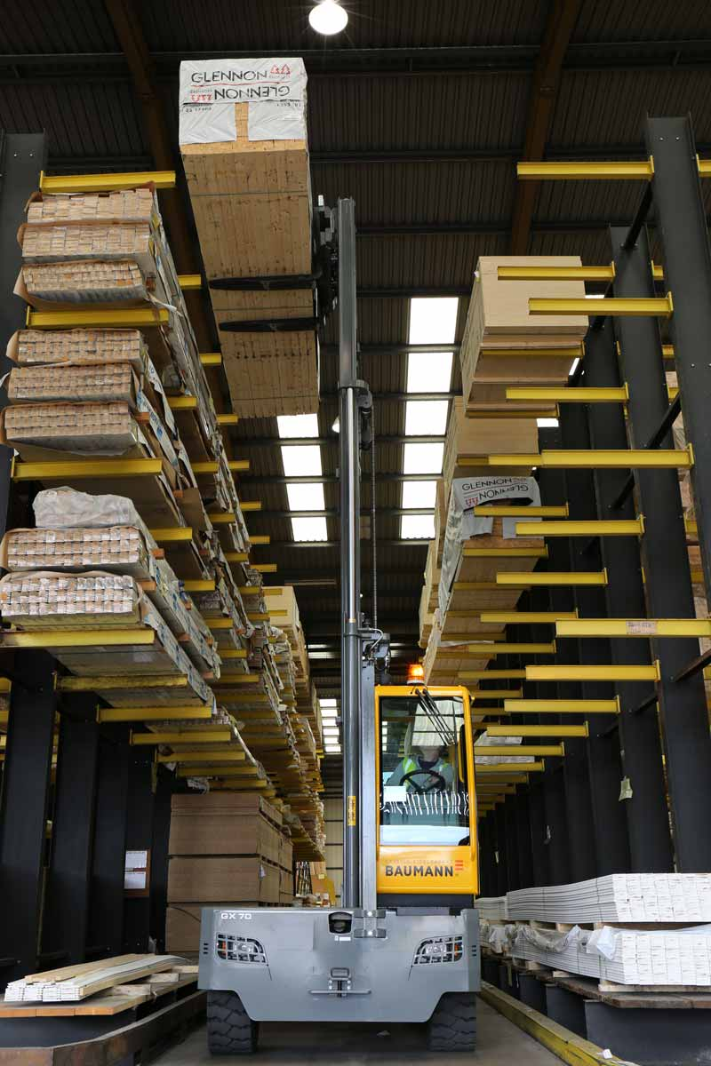 Baumann GX 70 sideloader lifting a bundle of lumber on to the top level of a cantilever rack